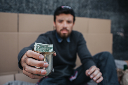 Poor and dirty man is sitting on the ground and looking on camera. He is holding a metal cup with dollar in it. He has to beg about help and mercy.