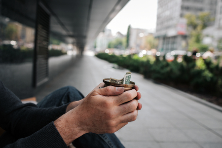 A piture of mans hands holding a cup with one bill. He is a beggar. Guy is sitting on the ground outside. He is lonely.