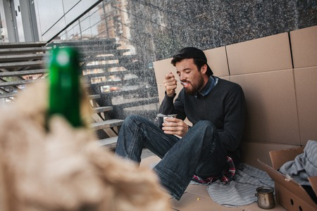 A picture of homeless man sitting on cardboard and eating food from can. Also there is a green bottle in brown paper in front of picture. Man is devouring food. Stock Photo
