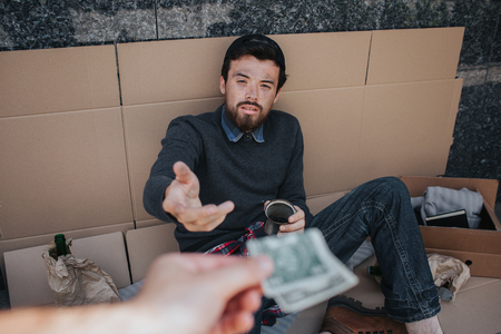 Tired beggar is sitting on cardboard and looking at hand that gives him money. Guy is reaching to it with his hand. Young person is in despair.
