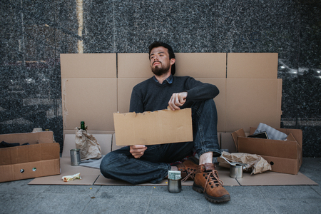 Hopeless and homeless person is sitting on cardboard on the ground and holding a piece of cardboard. He looks tired and sad. There is a metal cup with cash near mans legs and some more stuff as well.