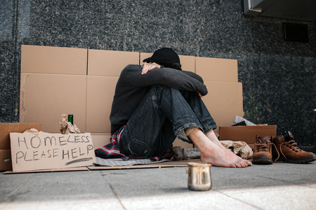 A picture of hopeless man sitting on the cardboard and hiding his face. He is covered it with hands and looking down. Man is sitting without shoes on. He is a beggar. There is metal cup for charity. Stock Photo