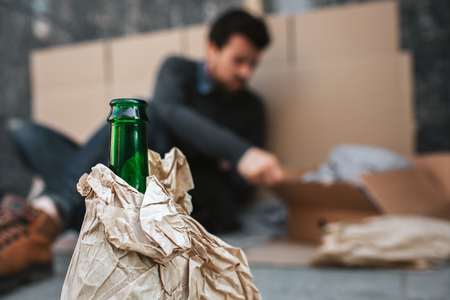 Camera is concentrated on green bottle standing in front of guy whos sitting on the cardboard and reaching the box. Body of bottle is covered with paper.