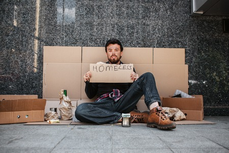 A picture of dirty man sitting on cardboard and looking straight. He is tired and exhausted. Guy is holding a homeless cardboard. THere are many things lying on the cardboard besides him.