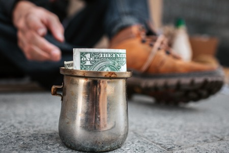 Close up of focused old metal cup standing on asphalt. There is a bill of one dollar inside of it. Hand is reaching the cup.