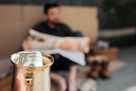 Camera is focused on metal cup with dollar in it. It is beggars cup. Homeless man is sitting on cardboard and reading newspaper. He is relaxing. Stock Photo
