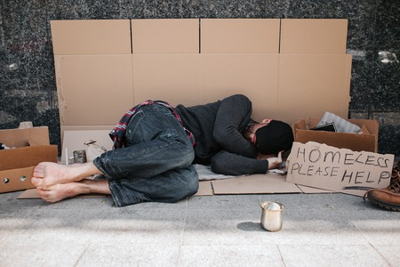 Helpless and defenceless man is lying on the cardboard on concrete floor and sleeping. He is covering his face with hands hiding it from the sun. There is a sign besides him says homeless please help. 版權商用圖片 - 102132364