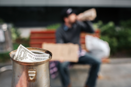 Camera is focused on metal cup. There is a dollar bill in it. Guy is sitting on the bench and drinking from bottle. It is his cup. Stockfoto