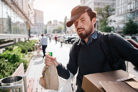 Stylish homeless man is standing outside on the street and holding a bottle that covered in piece of paper and a box. That is his stuff. Also man wears hat on the head. He is looking straight forward. Stock Photo