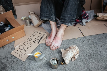 A picture of mans feet without shoes. Man is sitting on cardboard. He is a beggar. There is a sign which says homeless please help, metal cup with dollar and lot of other things.