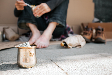 A picture of cup standing on concrete ground. There is a dollar in it. Also we can see beggars legs. He is holding a can with food in hands and spoon as well. There are lots of things lying on ground.