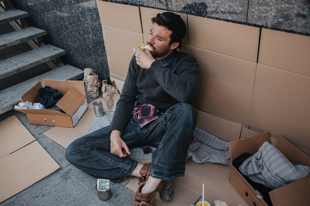Dark-haired and dirty man is sitting on cardboard and eating sandwich. His pose is relaxed. Guy is looking up. There is a lot of stuff that surrounds him.