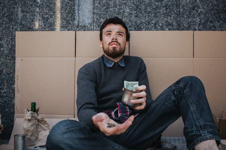 Adult beggar is sitting on cardboard and begging money. He is looking up. Man has some coins in one hand and a cup with some cash in another one. His sight is full of despair. Stock Photo