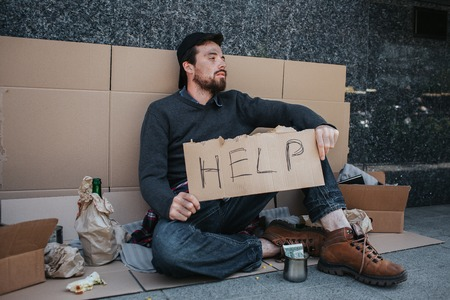 Dirty man is sitting on the ground and holding a help cardboard in hands. He is looking to the side. There are lots of stuff near him. Also there are a cup with money in front of him.