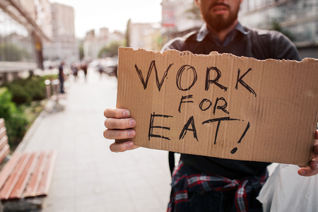 A picture of homeless man standing outside and holding a cardboard which says work for eat. Guy doesnt have a job and looking for it. Stock Photo