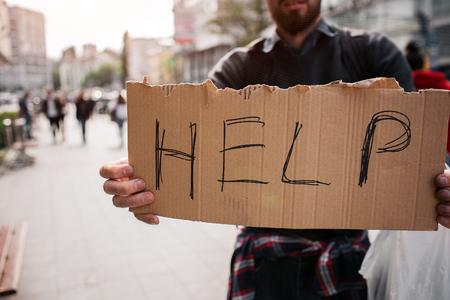 Another picture of cardboard which says help. It is hold by a jobless man. He is also a homeless man. He is looking for a compashion and money.