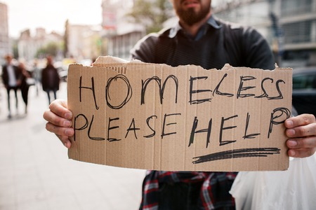 Bearded man is standing on street and holding a cardboard. It says homeless please help. Guy is looking for some mercy from other people and help as well. 版權商用圖片 - 102133537