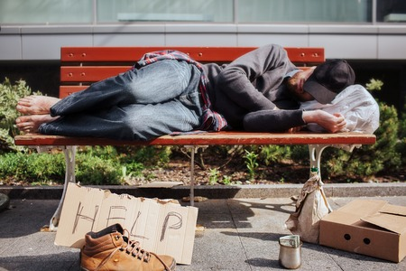 Homeless man is lying on bench and sleeping. Hee is tired and exhausted. There is a bag with stuff underneath his head. There is a help cardboard and a metal cup with money on the ground. Stock Photo