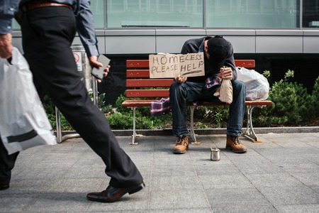 Poor and drunk man is sitting on bench and holding a cardboard which says homeless please help. He has put head on hand in which he has a bottle of drink. Guy is sleeping.