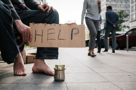 A picture of mans legs without shoes standing on the concrete ground. There is a metal cup with money on it. Guy is holding a cardboard which says help. Stock Photo