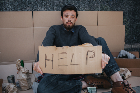 Portrait of homeless guy sitting on cardboard and holding a help cardboard in hands. He is looking straight at camera. There are lots of stuff and paper surrounding man.
