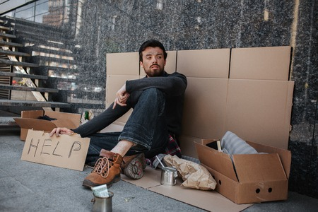 Sad and tired dark-haired man is sitting on the cardboard and holding another cardboard with the word help writing on it. He is looking aside. He is homeless. Stock Photo