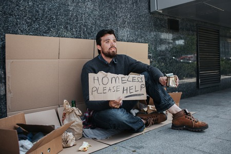 Homeless man is sitting on cardboard and and holding a sign that says homeless please help. He is begging money. Guy is in despair and needs help a lot. 版權商用圖片