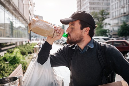 A picture of man standing on the street and drinking from bottle. He is homeless. Guy has a bag hanging on his hand and a box with different stuff.