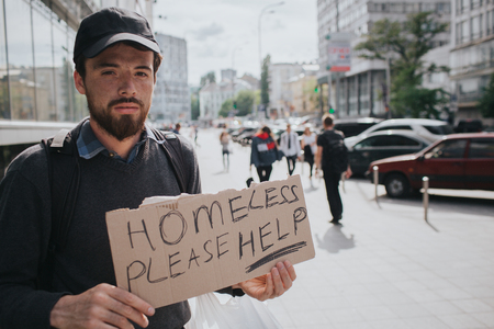 Homeless man is standin on the street and showing the sign which says homeless please help. Guy is waiting for somebodies help. He looks serious and tired.