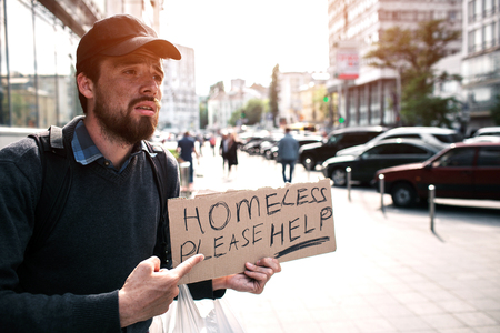 Guy is standing on the street and pointing on piece of cardboard which says homeless please help. Guy is begging for money and help. He is in despair.