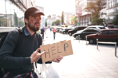 Poor man is stnading and pointing on cardbpard which says help. He is despair. Man doesnt have anybody to help him. He is looking for somebody to help him.