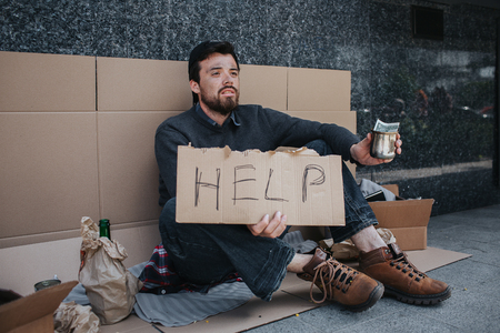 Dark-haired man is sitting on the cardboard and holding a sign that says help. He is holding in left hand a metal cup with one dollar in it. Guy has lots of stuff lying besides him.