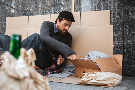 A picture of man sitting on the cardboard on the ground. He lives outside. Guy is reaching the box and looking into it. He is poor and lonely.