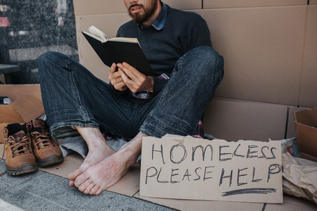 Smart homeless man is sitting on cardboard and reading a book. He is very concentrated on that. There is a sigh which says homeless please help. Stock Photo