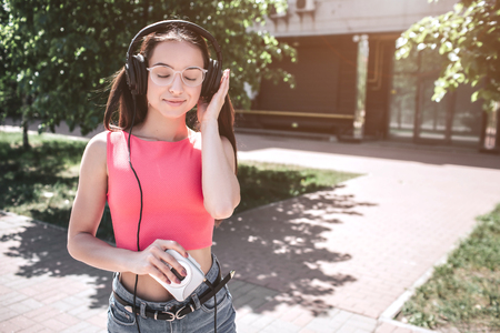 Beautiful girl is standing outside and listening to music in headphones. She is holding small and white player in right hand and kepping the other hand at the headphone. She likes listening music.