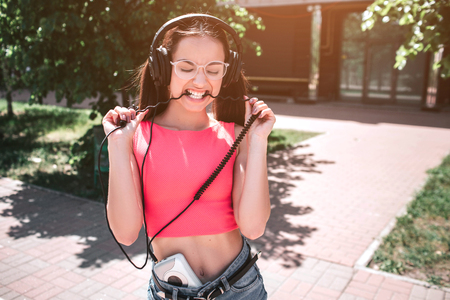Emotional girl is standing and stretching cord from headphones and biting it at the same time. She wears glasses. Young woman is keeping her eyes closed.