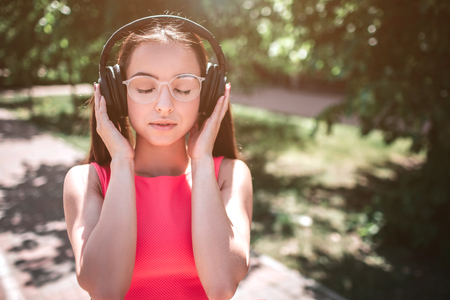 Nice portrait of beautiful girl standing on the street in a sunny day and keeping her eyes closed. She is holding her hands on the headphones trying to listen to music better.