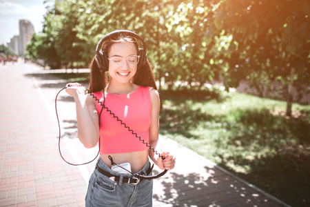 Attractive melomaniac is walking down the road and smiling. She is looking down and enjoying the moment. She is stretching the back cord from headphones. Stock Photo