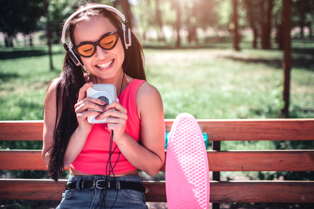 A portrait of happy and delightful girl sitting outside on bench and smiling. She is keeping her eyes closed. Girl is holding white player close to her head. Also she wears headphones.