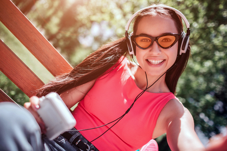Positive and happy girl in weird glasses is taking selfie. She is smiling to camera. Girl is listening to music through headphones.