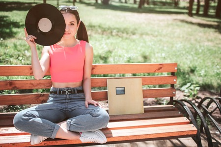 Nice and young girl is sitting on bench with her legs crossed and looking straight forward. She is holding vynil disk with hand and covering one eye with it. Also there is vynil hard cover on bench.