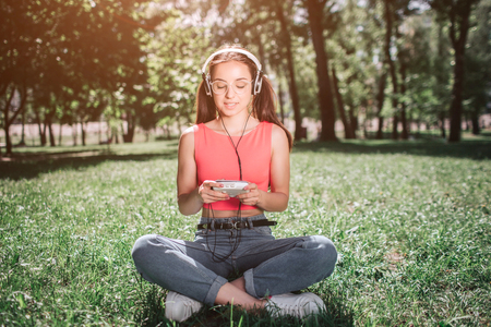 Peaceful and relaxed girl is sitting on grass with her legs crossed and listening to music. She has headphones on her ears. Girl is looking to music player and smiling.