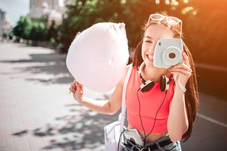 Beautiful and gorgeous girl is standing and posing like she is taking picture with her white camera. Also girl is holding a cotton candy in her hand.