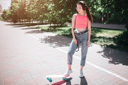 Beautiful and fantastic girl is standing on street in a sunny day and posing. She is holding one foot on skate.