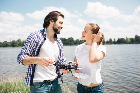 Lovely picture of young man and woman standing together and looking at each other. They are in love with each other. Guy is holding drone in hands. Woman is holding her hands on hair.