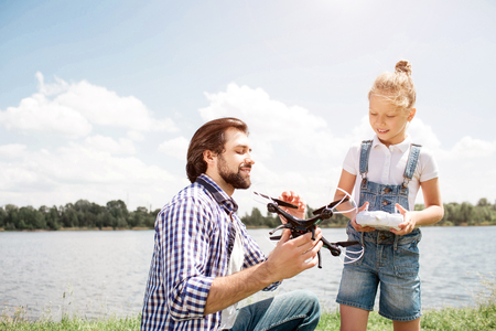 A picture of father and daughter spending time together. Guy is holding drone and showing it to girl while small kid has control panel in her hands. Child is looking at drone as well. Imagens