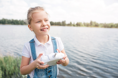 Little and cute girl is looking straight forward and holding white control panel in hands. She is standing at the edge of water. Child looks happy. Stock Photo