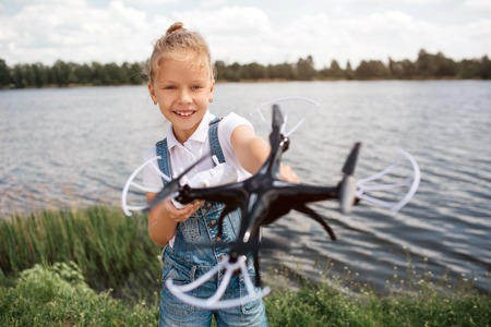 A picture of girl holding black drone i hands. She is looking at it. Girl is standing at the river shore. Imagens