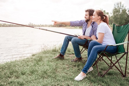 Two people are sitting at river shore. Guy is holding the edge of fish-rod and pointing on water while girl is looking at the same direction as guy is. They are very calm and peaceful. 写真素材