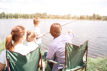 A picture from the back. Small boy is holding a fishing rod and trying to catch some fish in the river. His dad is guiding him and pointing forward. Woman is holding small girl on her lap.
